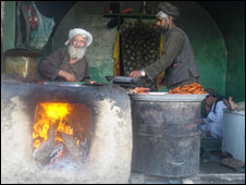 Stallholders cook bread and fish in Kandahar city