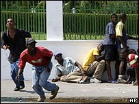 Haitian protesters run for cover from shooting outside the National palace in Port-au-Prince on 8 April