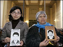 Relatives of 1992 massacre victims show photos of them (image from August 2007)