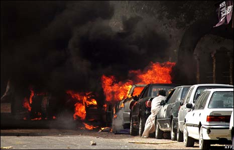 A man tries to remove a car near the burning vehicles at a street in Karachi on Wednesday