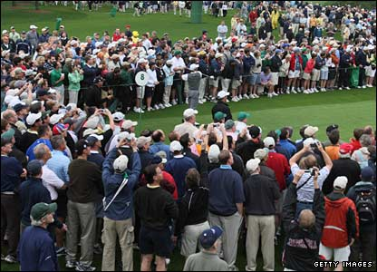 Tiger Woods (almost indistinguishable in a grey jumper) tees off, surrounded by a huge crowd