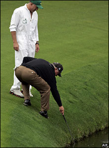 Mark O'Meara tries to retrieve a ball from the water, watched by Tiger Woods' caddie Steve Williams