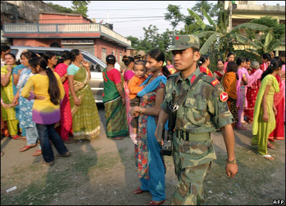 A Maoist soldier patrols the area outside a polling station where Prachanda voted