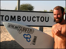 Mike Sternberg next to a sign for Timbuktu