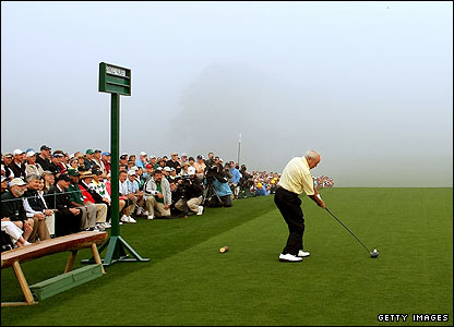 Arnold Palmer hits the ceremonial tee shot in misty conditions