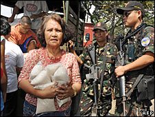 Residents queue for rice as soldiers guard distribution around Manila, 4 April 2008