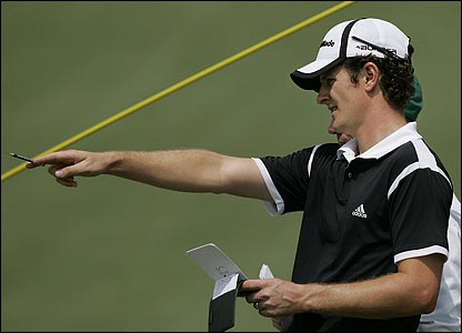 Justin Rose talks things over with his caddy