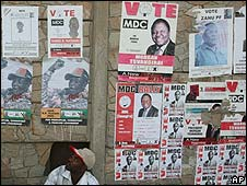 Zimbabwean man sits under election posters