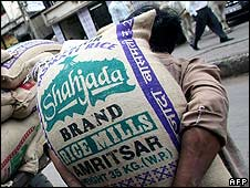 Indian labourer carries bag of rice in Delhi