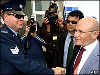 Mehmet Ali Talat shakes hands with a Greek policeman, 11 April 2008