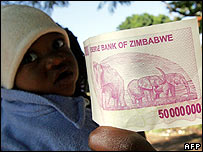 A person carrying a child and holding a Z$50m note (Photo: Alexander Joe/AFP/Getty Images)