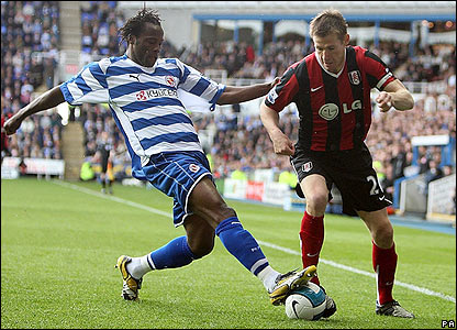 Reading's Andre Bikey and Brian McBride battle for the ball