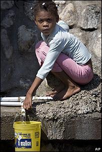 Una niña recoge agua potable en Puerto Príncipe