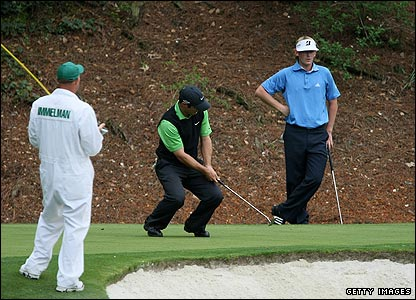 Trevor Immelman putts while Brandt Snedeker watches on