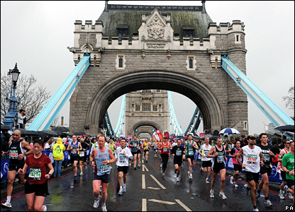 Runners along Tower Bridge in wet conditions