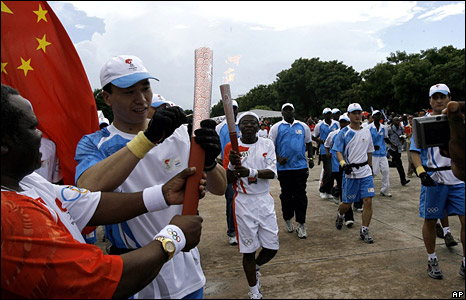A Chinese security guard ignites one of the torches used in the relay