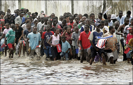 Spectators wade through the flooded streets as they follow the torch relay