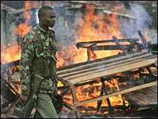 A police man walks past burning barricades set up by protesters in the Nairobi slum district Dandora