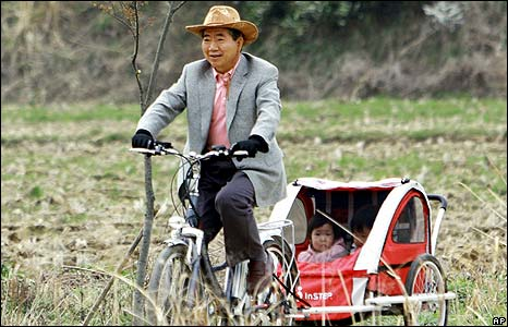 Former South Korean President Roh Moo-hyun takes his grand-daughters on a cycle ride.