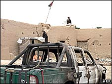 An Afghan man sits on top of a police checkpoint alongside a police vehicle burnt out by the Taliban in the Arghandab district of Kandahar province on April 14, 2008