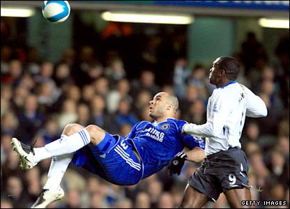 Alex, under pressure from Wigan's Emile Heskey (right), clears the ball