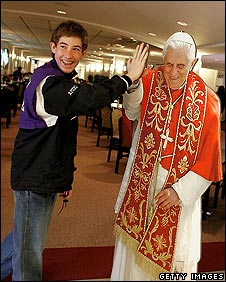 William Cove, 15, gives a high-five to a six-foot-tall photographic cut-out of Pope Benedict XVI in a gift shop