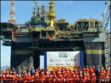 Petrobras workers in front of an oil platform