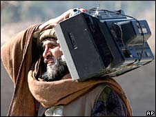 An Afghan man carries his broken television for repairing on the outskirts of Jalalabad