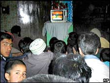 Afghan people watch a movie inside a video shop in Kabul