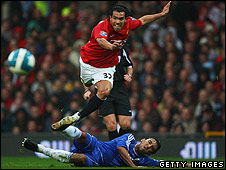 Carlos Tevez is tackled by Paulo Ferreira