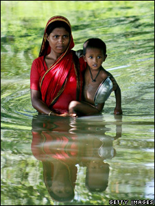 Mother and child wading through floodwater (Getty Images)