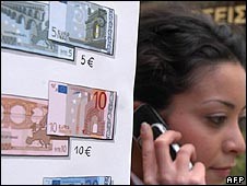 Woman speaks on her phone next to currency exchange signs