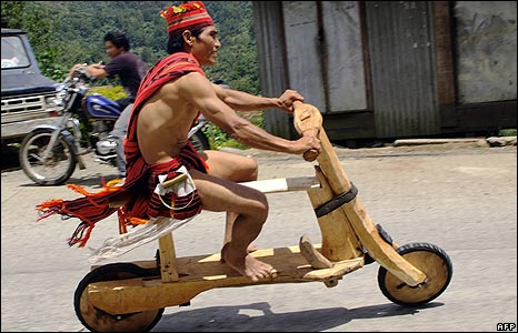 An Igorot tribesman rides his wooden scooter