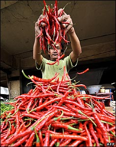 A grocer arranges his display of chilli peppers