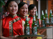 Waitresses carry bottles of Snow beer in a restaurant in China