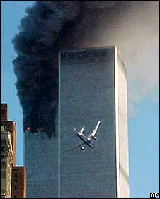 An airliner flies into the World Trade Center's south tower as the north tower burns on 11 September 2001