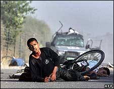 Wounded Palestinian youths lie on the road near the car in which the Reuters cameraman was travelling
