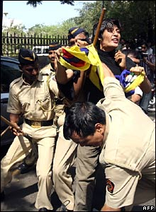 A Tibetan exile shouts slogans as he is apprehended by security personnel