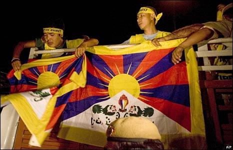 Tibetan protestors wave their flags from a police vehicle after being detained by Indian police