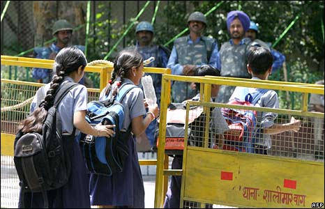 Indian school-children cross a secuirty barricade as paramilitary forces stand alert outside the Le Meridien Hotel