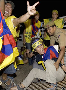 A Tibetan exile shouts slogans as he is apprehended by security personnel for attempting to breach a security cordon