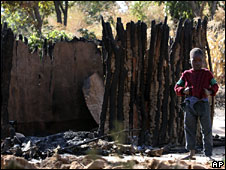 Boy in front of burnt hut