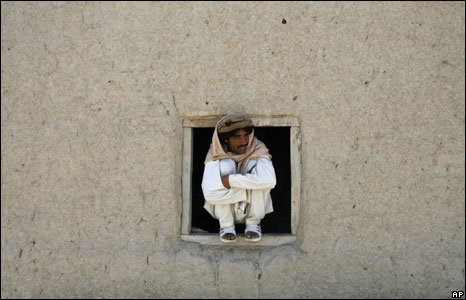 A man in Khost province, Afghanistan, 17 April 2008, watches patrol by 101st Airborne Division