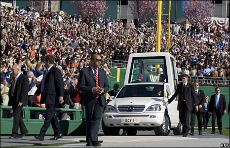 Secret service operatives surround the Popemobile as Pope Benedict arrives for Mass at the Nationals stadium, Washington DC, 17 April 2008