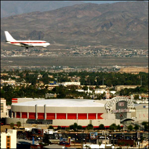 A plane flies over the Thomas and Mack Center
