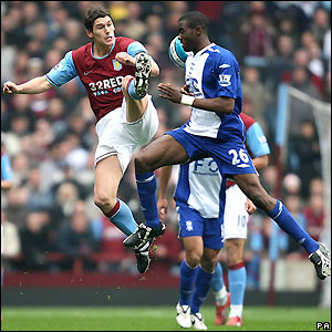 Villa's Gareth Barry contests possession with Fabrice Muamba
