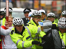 Officers tackle a protester during Olympic torch relay in London
