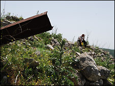 Hana Nasser sitting on the ruins of his former home