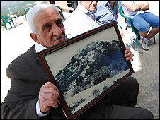 Asad Daoud holds up a pre-1951 picture of Iqrit village