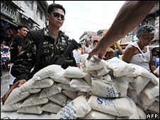 A soldier stands guard over subsidised government rice sold in Manila, the Philippines, 16 April 2008